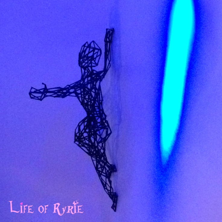wire sculture of a human reaching out from wall
